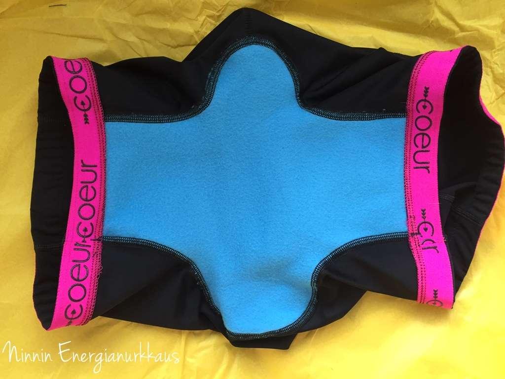 Sininen saumaton pehmuste ylettyy lahkeen suihin asti. Pinkit jää ihoa vasten, ei ulkopuolelle mustat housut.